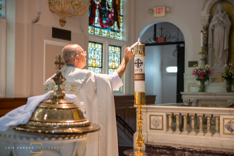 Priest lighting the candle during baptism