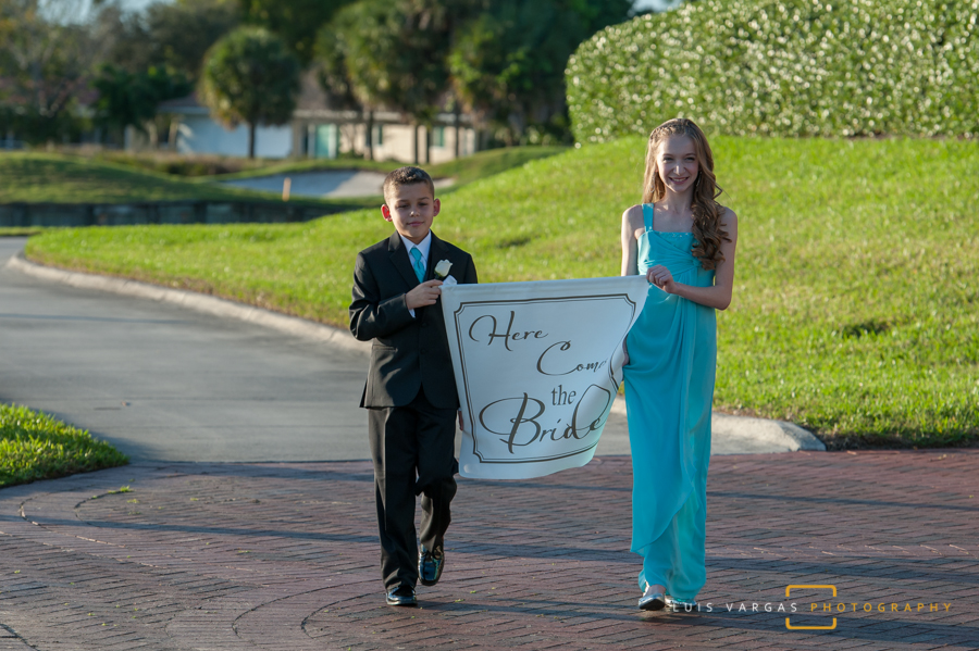 Kids bringing the bridal sign down the isle