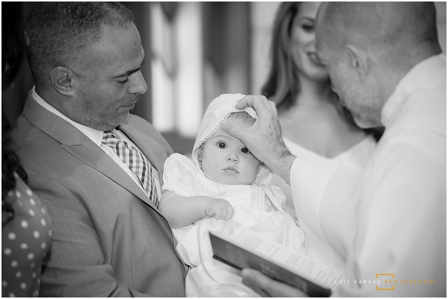 The priest blessing baby Elle