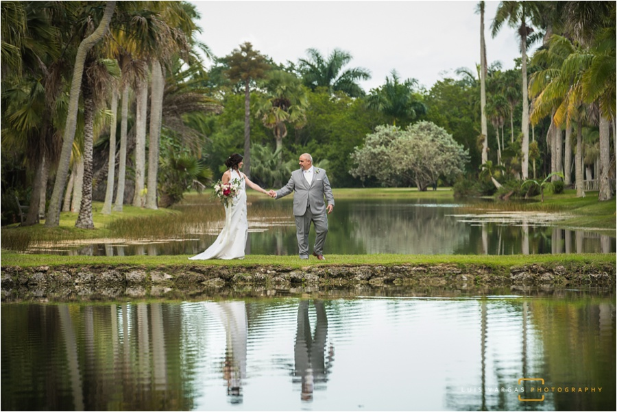 Bride and groom taking portraits around the lake